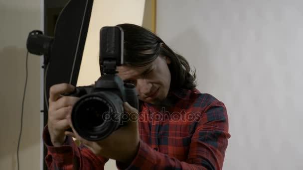 junger Fotografiestudent mit dunklen Haaren an seinem ersten Arbeitstag in einem professionellen Studio, der die Kamera vor der Fotosession überprüft