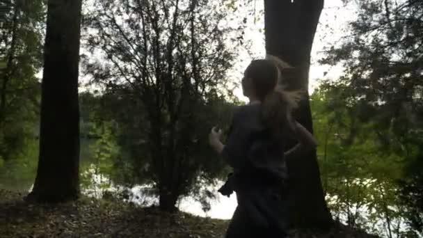 Modello di fitness femminile atletico che corre lungo il lago in natura per aumentare la resistenza cardio al rallentatore