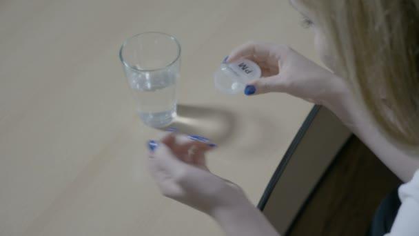Aufgebrachte Frau, die am Tisch sitzt, lässt ein Schmerzmittel in ihre Hand fallen und schluckt es zu Hause mit Wasser, um ihre Kopfschmerzen zu heilen