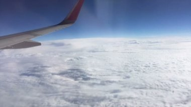 Aerial view out of window of amazing clouds skyline and flying airplane wing
