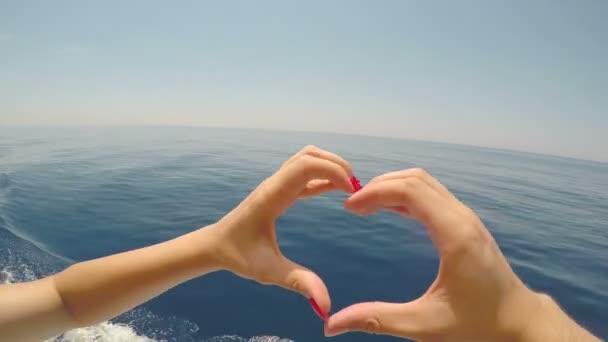 Pár rukou dotknete prsty tvoří tvar srdce s krásným modrým mořem a letní obloze v pozadí
