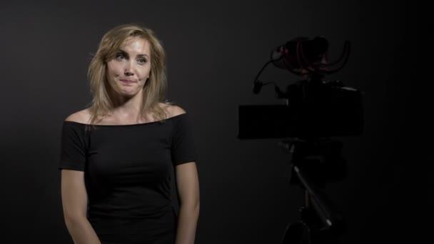 Gyönyörű női új professzionális videó forgatás kamera blogjában stúdióban