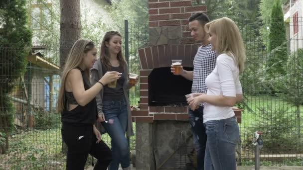Millennials Freunde Anhebung Biergläser für einen Toast mit Spaß bei der Party im Freien in der Nähe von Grill im Garten