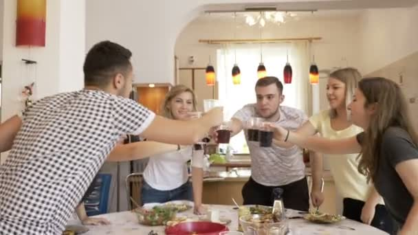 Gathered happy friends sitting at table in the kitchen toasting and cheering enjoying time together at home party with snacks and cola