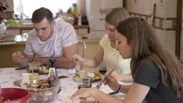 Teenage hlad přátel stáli spolu v kuchyni u stolu, těší vkusné nezdravý oběd jíst sacharidy a pečené maso, pití cola