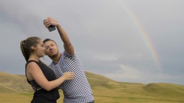 Szenvedélyes pár tini szerelmesek smartphone selfies pics véve, és a festői táj panoráma szivárvány fényképezés