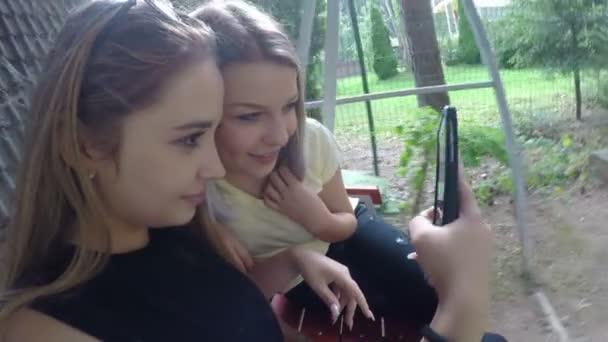 Tizenéves női meg hűtés csinál vicces selfies pics smartphone kertben hinta