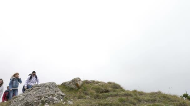 Radostné skupina přátel, lezení nahoru a dosáhl vrchol hory, skákání a zvyšování paže těší úspěch jejich dosažení