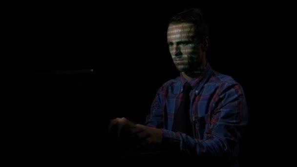 Nadšený a překvapený muž hacker zaměření a zadávání kódů, které jsou promítány na obrazovce na obličeji