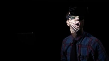 Young businessman at home in the dark wearing virtual reality technology goggle glasses to play a maze game