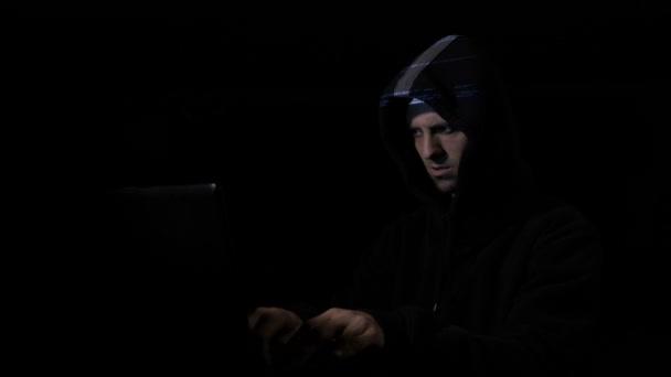 Zlost, úzkost hacker počítačový programátor v hood útočit kybernetické bezpečnosti serverů a kývl přitom digitální data se odráží na obličeji