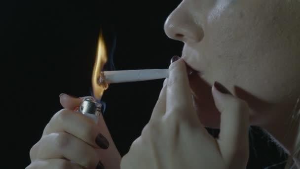 Egy depressziós szőke tinédzser lány ül a sötétben belélegzése és exhaling füst füvet cigarettát, villámcsapás közelről