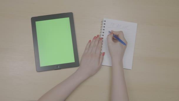 Felülnézet nő kezében vörös körmök, szabad idő, és a tervezés egy zöld képernyő tabletta pc és notebook írás teendők