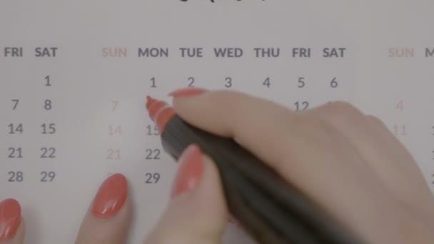 Draufsicht der weiblichen Hände Unterzeichnung Periode Menstruation Tage im Kalender mit einem Marker rot