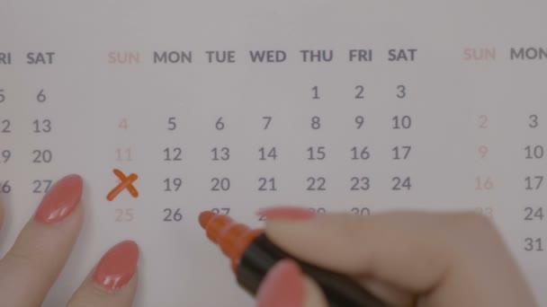 Pohled shora serveru žena rukou s červenými nehty rámuje dní v kalendáři s barevným značkovačem