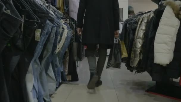 Tall fashionable male model wearing black coat walking in a store shopping in search for clothing accessories