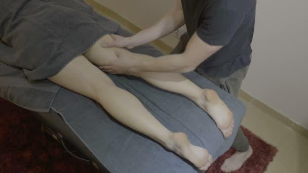 Nahá dívka se ručníkem a ležící na posteli dostat nohy masáž v lázeňském centru hotelu od profesionálního maséra