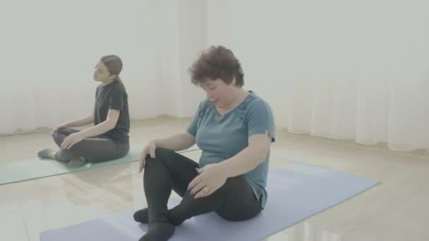 Középkorú nők forgatható fej ül egy matracot a bemelegítés előtt jóga gyakorlatok