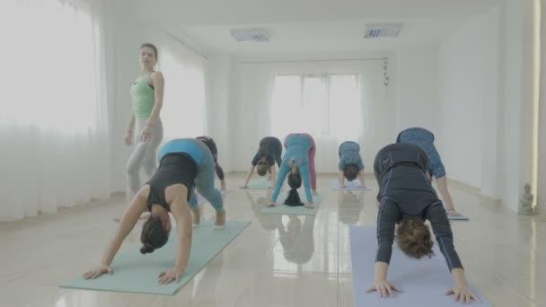 Középkorú nők dolgoznak ki, míg a harcos póz gyakorlása során a jóga oktató, egy fitness-stúdióban csoportja