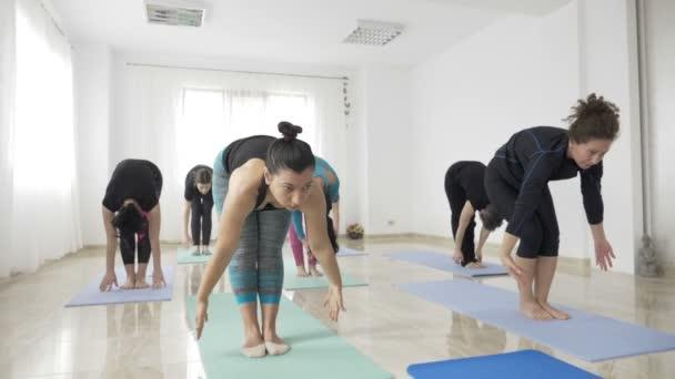 Állandó és nyújtás gyakorlatok segítségével szőnyegek, az emeleten egy világos fitness stúdióban, lassítva ezzel pilates jóga