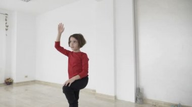 Beautiful fit female instructor teaching a little girl standing still yoga poses in slow motion in a bright gym studio