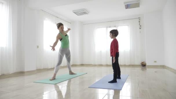 Egy gyönyörű fiatal anya tanítás neki lánya jóga, pilates gyakorlatok segítségével lábtörlőt, egy világos wellness stúdió lassítva