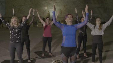Corporate women participating to a teambuilding inside a place made of salt walls and statues while standing on a fitness mat and practicing pilates and nirvana