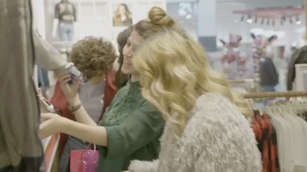 glücklich gestylte multikulturelle gemischte Rasse Freundinnen prüfen eine Designertasche und betrachten Kleidungsstücke, um in einem Markengeschäft im Einkaufszentrum einzukaufen