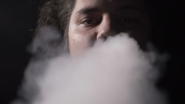 Kampány a fiatal férfi színész hosszú haj vaping elektronikus cigaretta a dohányzás, és fúj a kamerába, ban lassú steam felhő