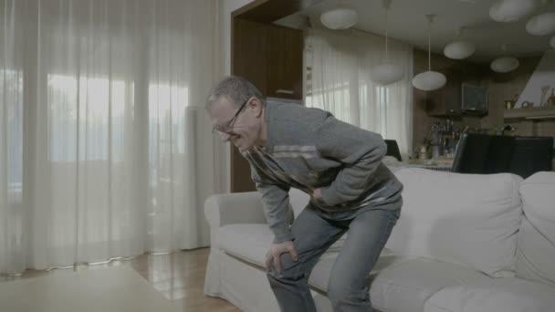 Starší muž doma vyjadřuje utrpení kvůli trávení nepohodlí a žaludku zánět dotýká břicho
