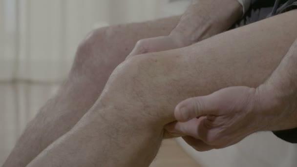 Starý muž masážní artritické koleno s kloubů doma