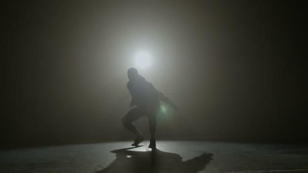 Silhouette einer talentierten jungen Tänzerin, die auf einer Bühne vor dem Rampenlicht Hip-Hop-Streetdance tanzt