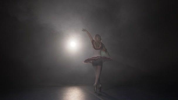 Ballerina in weißem Tutu und Spitzenschuhen tanzt und probt für die große Show in einem Studio mit Rauch in Zeitlupe