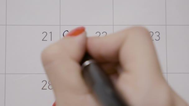 Mladá dospívající dívka v úmyslu jít do tělocvičny den v kalendáři a psaní připomenutí černým perem