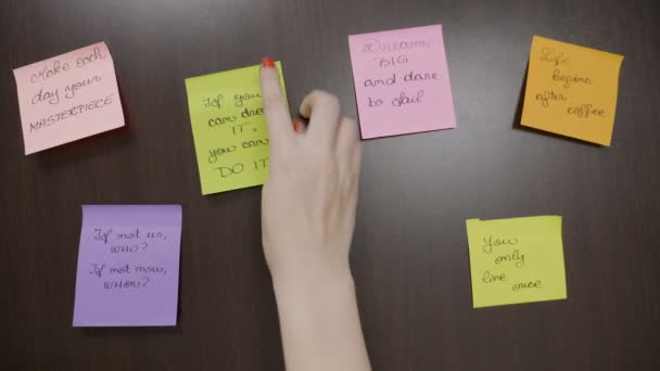 Young Teenager Girl With Red Nails Sticking Two Post It Notes That