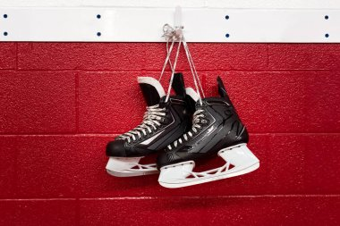 Hockey skates hanging over red wall with copy space