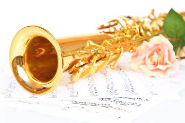 Pink rose, saxophone and music sheet