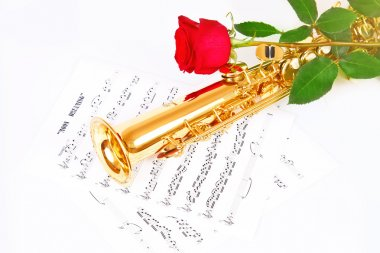 Red rose, saxophone and music sheet