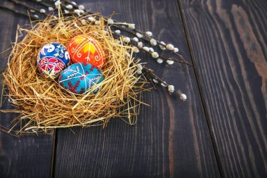 Easter eggs in a nest with willow twigs on a wooden table.