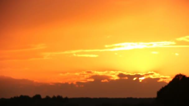Západ slunce s oranžové barvy nad polem. Pěkné mraky nakonec.