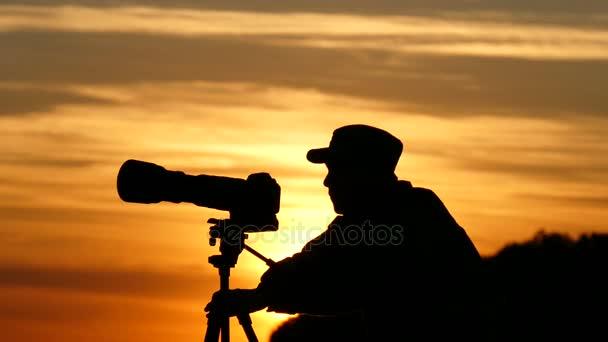 Silhouette des Kameramanns während des Sonnenuntergangs, die Summen zeigt.