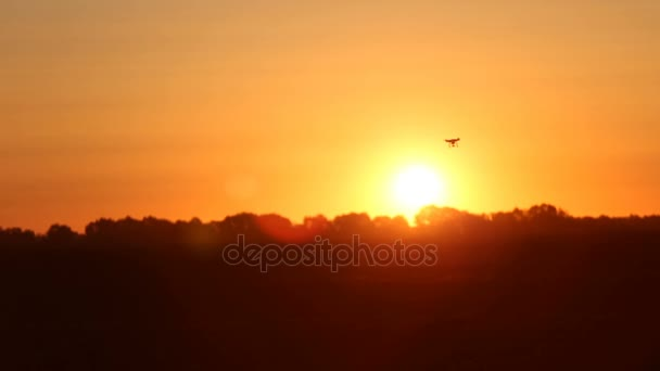 Kvadrokoptéra v rozostření létající kolem slunce při západu slunce.