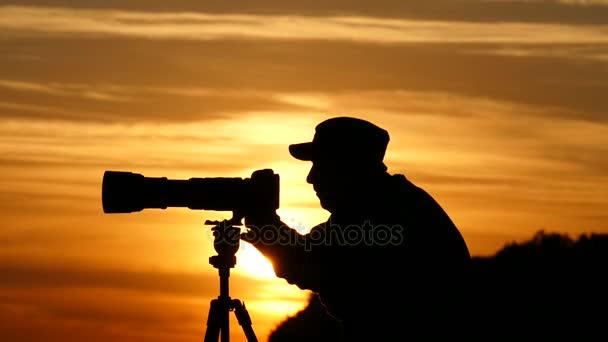 Silueta kameraman při západu slunce.