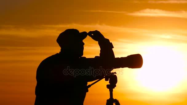 Silhouette of cameraman during the sunset. Man using focus ring.