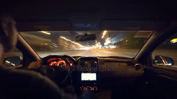 Muž řídil auto v městě večer. Širokoúhlý záběr