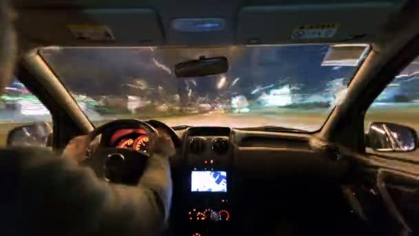 Abstraktní časová prodleva člověka řídit auto v městě večer. Širokoúhlý záběr