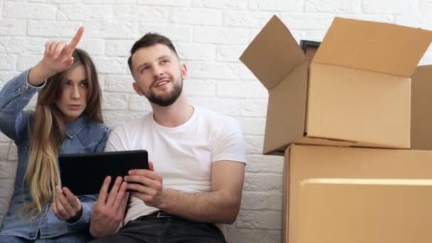 Šťastný pár hoblovaný nový interiér. Pomocí digitálních tabletu. Jezdec výstřel.