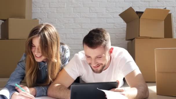 Sorridente, coppie di risata con tavoletta digitale e disegno (piano) della loro nuova casa. Rilocazione. Dispositivo di scorrimento girato