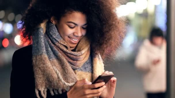 Mladá žena drží smartphone na ulici, dívá se na to a píše smsky.