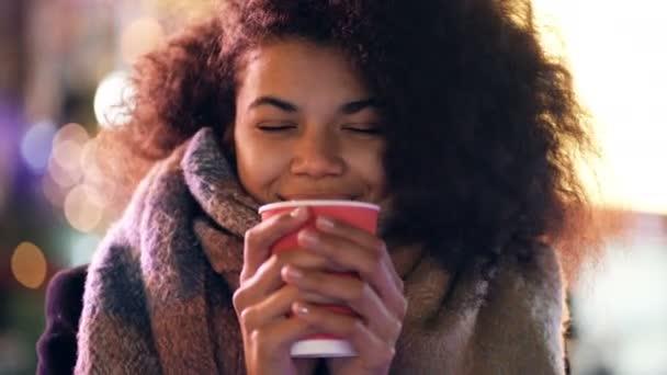 Detail portrét mladé afro-americké ženy stojící s horkou kávou venku. Úsměv, pocit útulnosti a pohled do kamery.